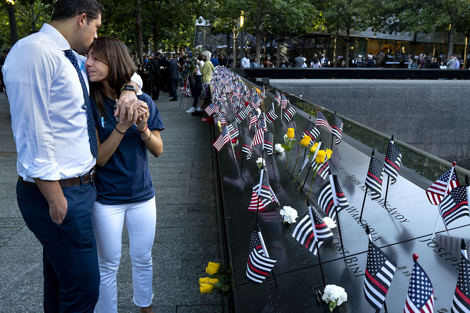 Katie Mascali is comforted by her fiance Andre Jabban as they stand near the name of her father, Joseph Mascali, a firefighter who was killed on 9/11, during a ceremony at the National September 11 Memorial & Museum commemorating the 20th anniversary of the terrorist attacks on the World Trade Center in New York City on Sept. 11. Craig Ruttle/Getty Images