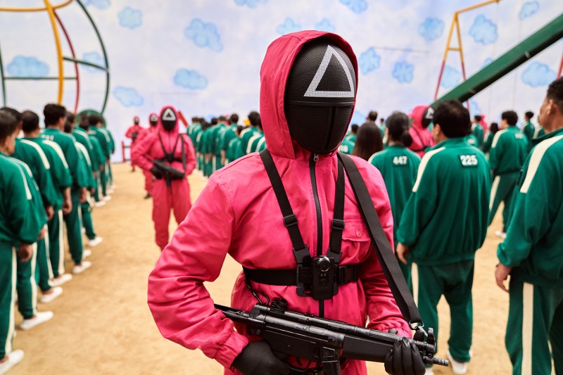 Masked armed guards keep watch over contestants during one of the show's deadly playground games.