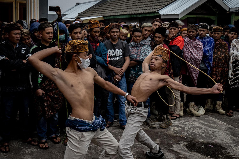 Tenggerese men perform Ojung fighting with rattan sticks in Lumajang, Indonesia, on Sept. 8. Robertus Pudyanto/Getty Images