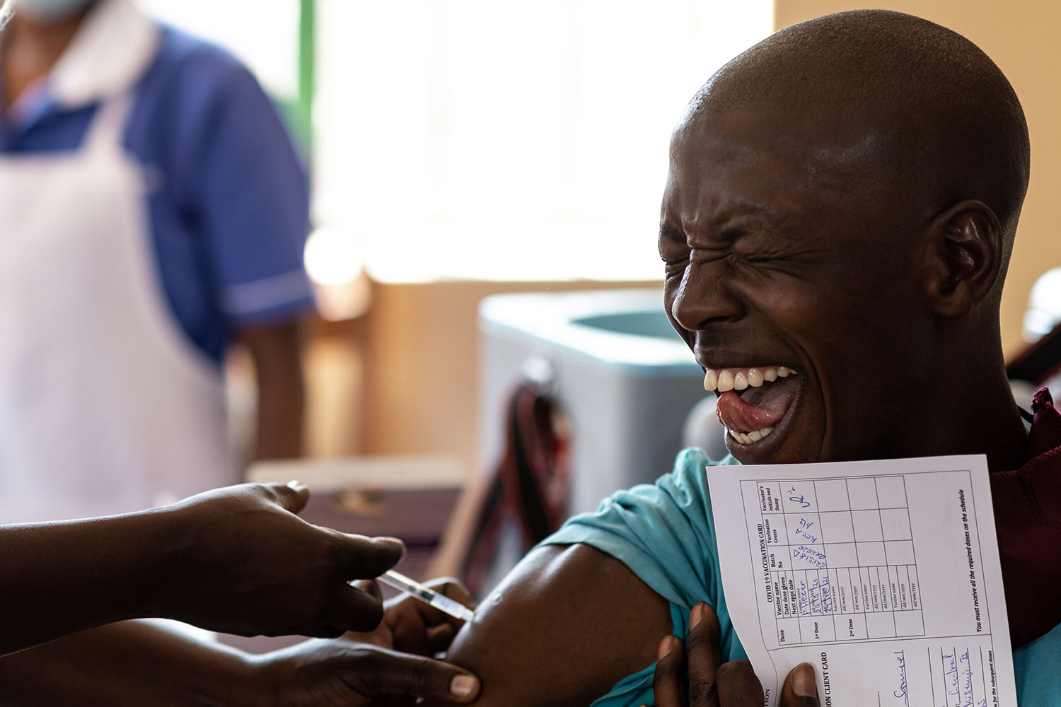 A patient reacts as a nurse injects the Pfizer coronavirus vaccine at a school as part of a new rollout of doses received from the U.S. government in Kampala, Uganda, on Sept. 29. Luke Dray/Getty Images