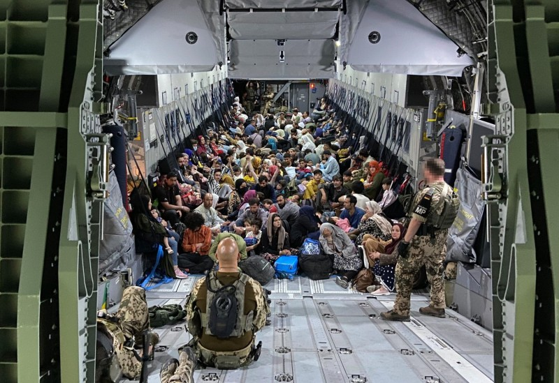 Evacuees from Aghanistan sit inside a military aircraft as they arrive at the airport in Tashkent, Uzbekistan, on Aug. 22.