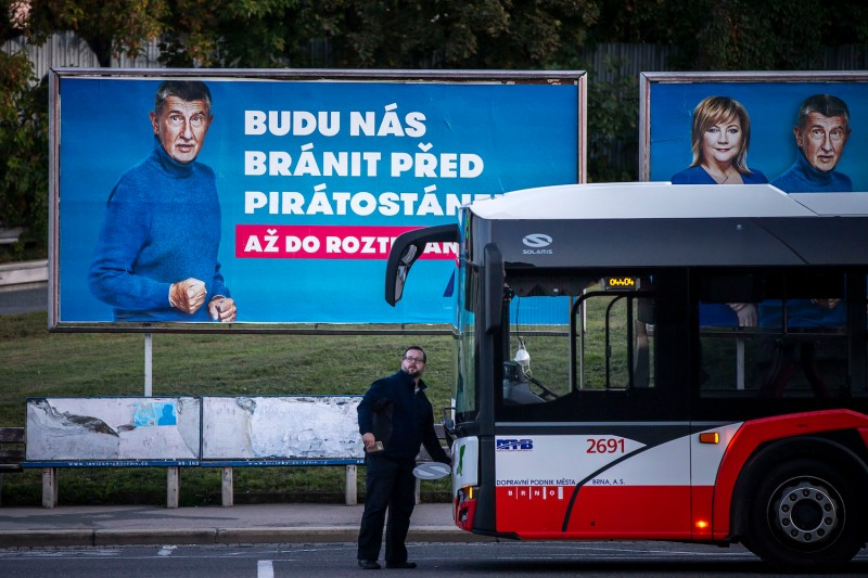 A man stands by a campaign poster for Czech Prime Minister Andrej Babis.