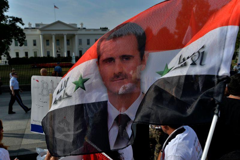 Supporters of Syrian President Bashar al-Assad wave a Syrian flag.