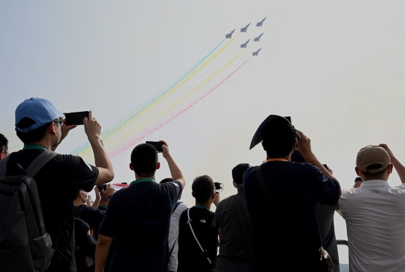 People watch a flight demonstration of Chengdu Aircraft Corporation's J-10s, made for for the People's Liberation Army Air Force, in Zhuhai, China.