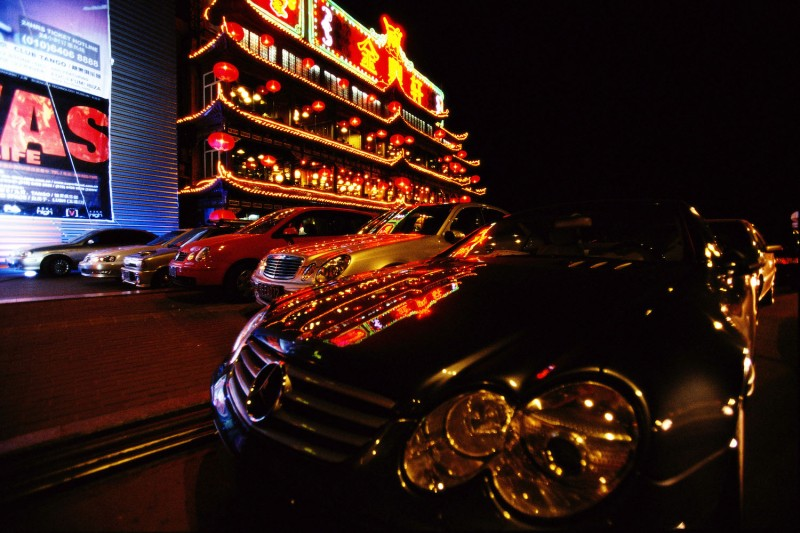 A collection of luxury cars stands outside a restaurant lit up with neon lights at night.