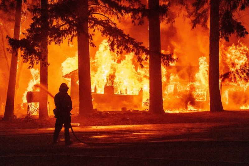A firefighter sprays water on a propane tank as a home burns due to the Dixie fire in Plumas County, California, on July 24.