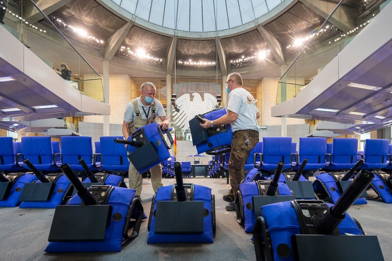 Workers rearrange the chairs in the plenary hall of the German Bundestag to fit the new seating arrangement for the parties in parliament after the recent election, in Berlin on Oct. 15.