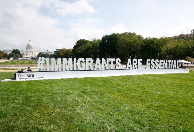 An art installation feature the phrase #ImmigrantsAreEssential in large white letters sits on the grass of the National Mall with the U.S. Capitol in the background.