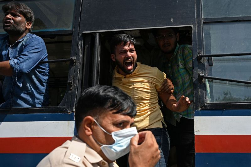 Activists shout slogans from a bus after being detained by police during a protest near the residence of Indian Home Minister Amit Shah in New Delhi on Oct. 9.