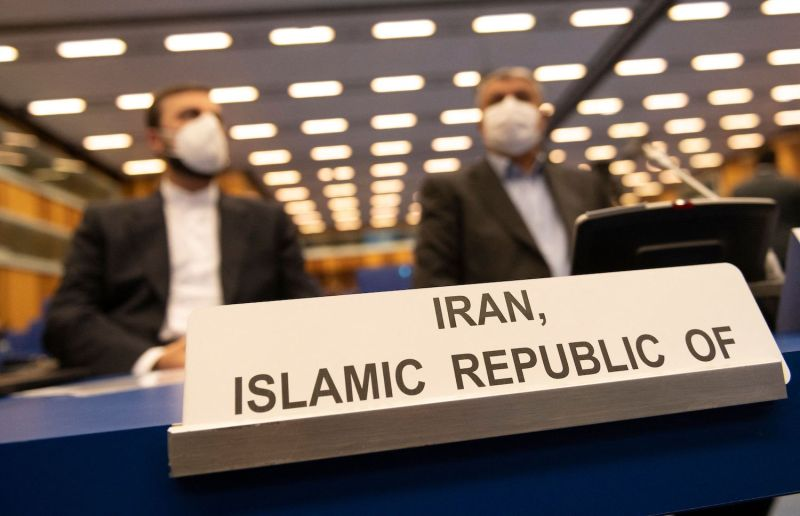 """Two men sit behind a sign on a table that reads """"Iran, Islamic Republic of."""""""