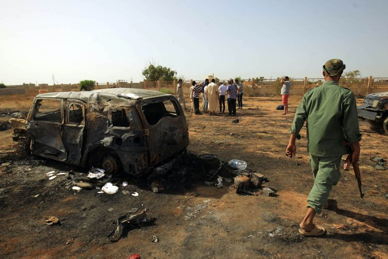 Libyans inspect the site of a car bomb attack.