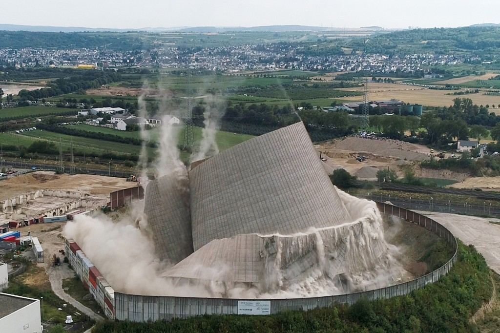 The cooling tower at the Muelheim-Kaerlich nuclear power plant collapses during a controlled demolition near Koblenz, Germany.