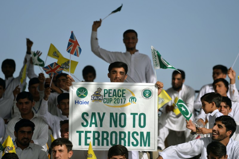 A Pakistani spectator carries a placard denouncing terrorism.