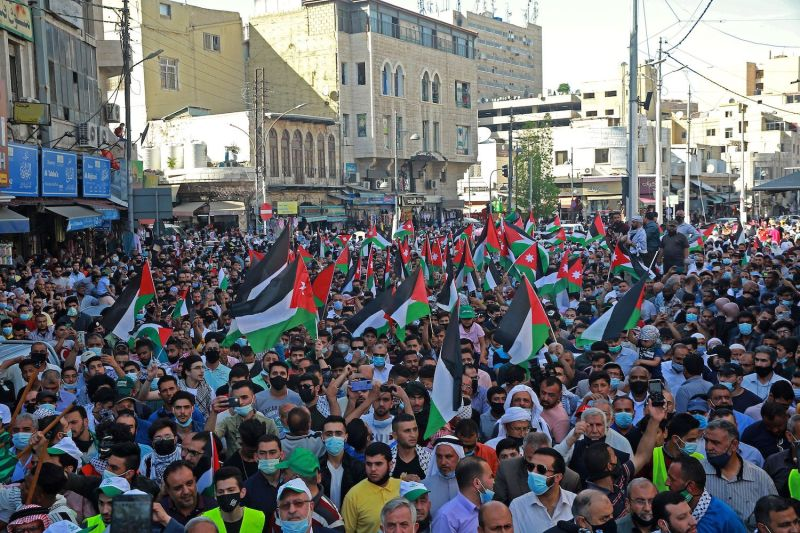Demonstrators lift flags during a protest to express solidarity with the Palestinian people in Amman, Jordan on May 16.