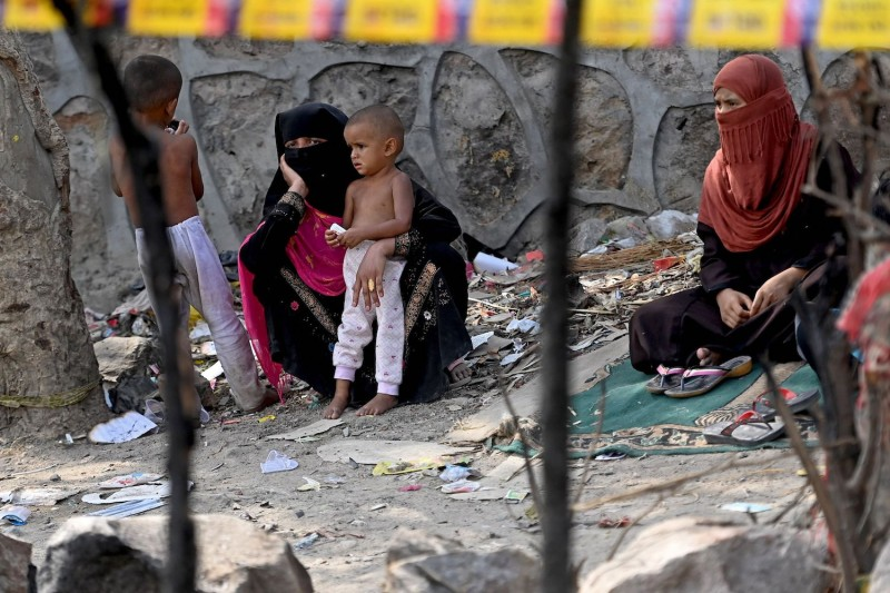 Rohingya refugees sit outside an area marked by police at their camp in New Delhi after a fire broke out there on June 13.