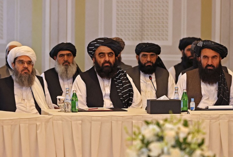 Members of the Taliban, all men, sit at a fancy table.