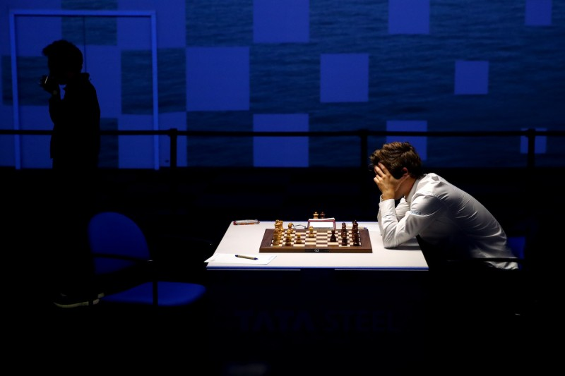 A man holds his head in his hands while looking down at a chess board.