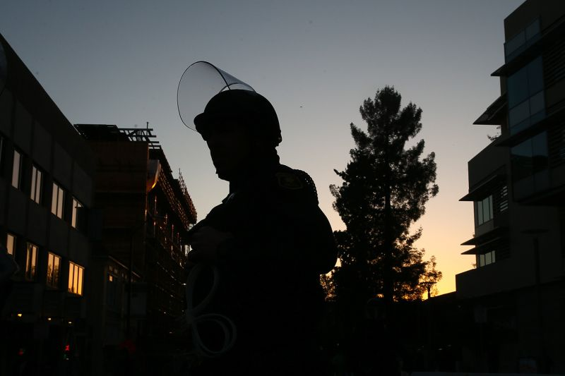 A police officer is silhouetted.